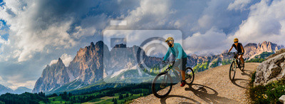 Naklejka Cycling woman and man riding on bikes in Dolomites mountains andscape. Couple cycling MTB enduro trail track. Outdoor sport activity.