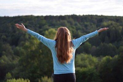Czerwone włosy Młoda dziewczyna w niebieskim sweter rozprzestrzeniania rąk. Widok z tyłu. Krajobraz Góry Las Tła. Wolność Podróży Inspiracji Koncepcji