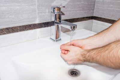 Człowiek myje ręce w łazience.