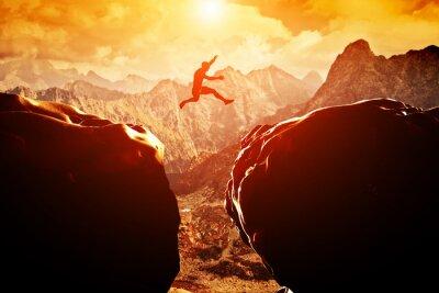 Naklejka Człowiek przeskakując nad przepaścią między dwiema górami na zachodzie słońca