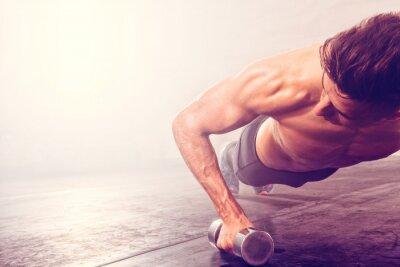 Naklejka Człowiek robi push-up ćwiczenia z hantle. Silny mężczyzna robi treningu CrossFit.