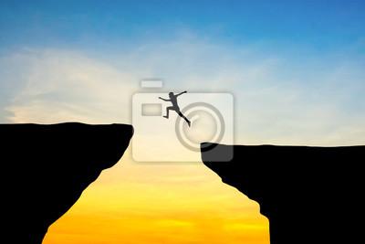 Naklejka Człowiek skok przez szczelinę między hill.man skoków na klifie na tle zachodu słońca, pojęcie pomysł na biznes