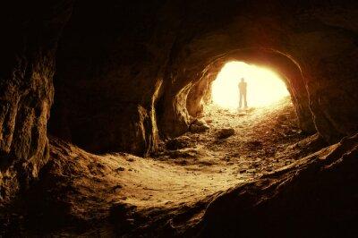 Człowiek stojący przed wejściem do jaskini