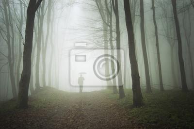 Człowiek z parasolem chodzenie do światła w mglistym lesie