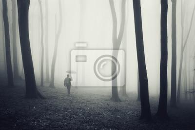 Człowiek z parasolem spaceru w ciemnym lesie z mgły
