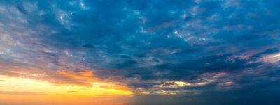 Dark clouds and orange sun at sunset