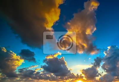 Dark clouds and shining sun at sunset