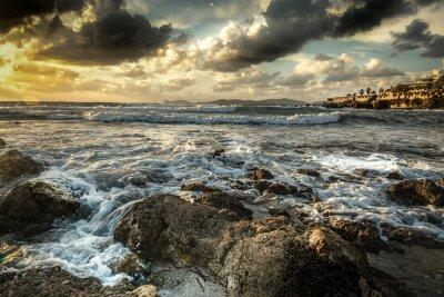 Dark clouds over Alghero coast at sunset