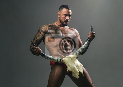 Naklejka Desire is the energy force. Sexy latino man showing his sexual desire and attraction. Muscular hispanic man with fit body holding skull and horns. Attractive power and desire force. Desire concept