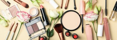 Naklejka Different makeup cosmetics and flowers on beige background. Female accessories
