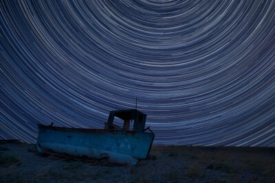 Naklejka Digital composite image of star trails around Polaris with Abandoned fishing boat on beach landscape