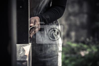Dłoń trzymająca papieru ściernego, polerowanie czarnej powierzchni drewna, nasycony odcień koloru
