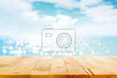 Naklejka Drewniany stół blur na rozmycie musujące wody morskiej i latem nieba tle