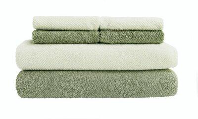 Duże i małe zielone ręczniki kąpielowe w stosie. Pojedynczo na białym tle