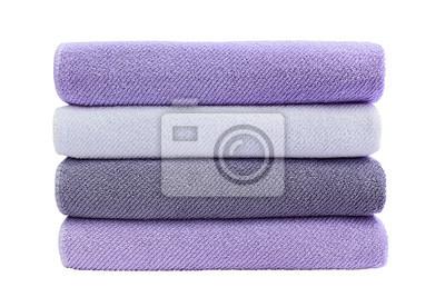 Duzi fiołkowi kąpielowi ręczniki w stercie odizolowywającej nad białym tłem