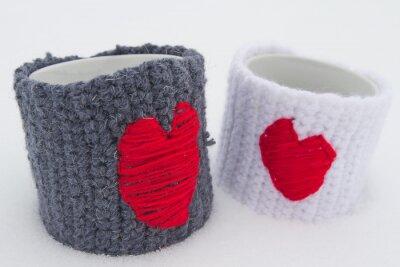 Dwa kubki z czerwonym serca na śniegu.
