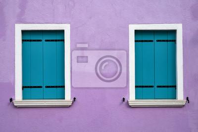 Dwa okna z jasnymi niebieskimi okiennicami na bzu ścianie. Włochy, Wenecja, wyspa Burano.