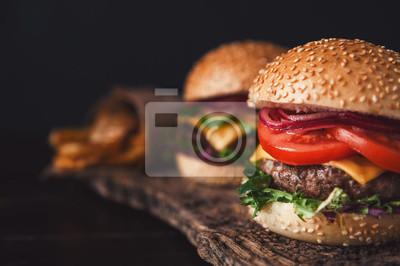Naklejka Dwa przepyszne, pyszne homemade hamburgery używane do siekania wołowiny. Na drewnianym stole.