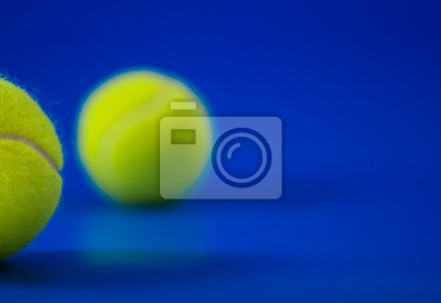 dwie nowe piłki tenisowe na niebieskim boisku ze światłem od lewej, cień i kopia po prawej