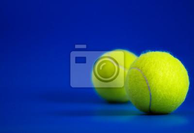 dwie nowe piłki tenisowe na niebieskim boisku ze światłem od prawej, cień i kopia po lewej