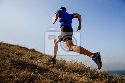 Naklejka dynamiczne uruchomiony pod górę na szlaku samiec lekkoatleta runner widok z boku