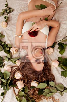 dziewczyna, która leży w bieliźnie na łóżku z róż