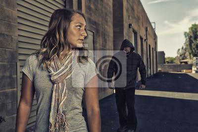 Naklejka Dziewczyna, która zna się na samoobronę, widzi mężczyznę idącego za nią.