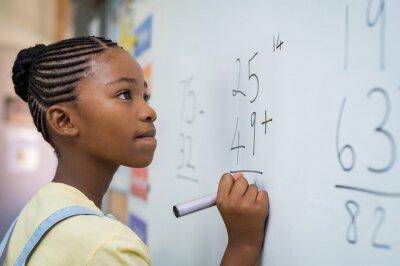 Naklejka Dziewczyna rozwiązuje matematyczny dodatek