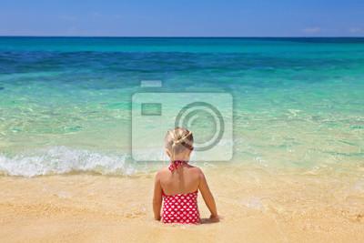 Dziewczyna siedzi na plaży piasku