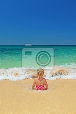Dziewczyna siedzi w oceanie Przełamując fale na plaży piasku