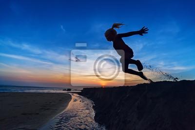 Dziewczyna skoków na plaży o zachodzie słońca