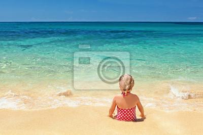 Dziewczyna w czerwonym stroju kąpielowym siedzi na piasku na plaży krawędzi