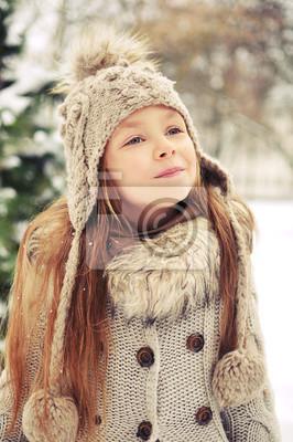 Dziewczyna w wełnianej czapce z frędzlami wokół śniegu i zimy
