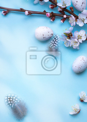 Easter greeting card with colorful easter eggs and sprin flowersl on blue table. Top view with space for your greetings - Image
