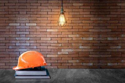 Edukacja inżyniera concept.Orange kasku na książki i tła cegła ściany żarówki światła światła