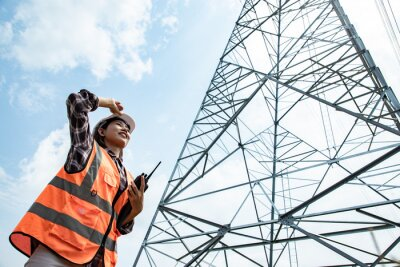 Naklejka Electrical Asian beautiful engineer with high voltage electricity pylon and using walkie talkie and tablet to control assistant. Electrical power lines and towers at blue sky.