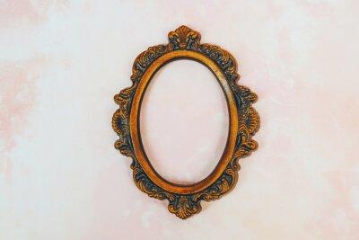 Naklejka Empty bronze vintage round picture frame on light pink canvas background.
