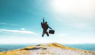 Naklejka Excited young businessman jumping keeping arms raised hiking the mountain peak - Celebrating success, winner and leader concept