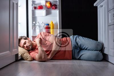 Naklejka exhausted man sleeping on floor in kitchen near open refrigerator