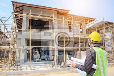 Naklejka Fachowy inżyniera architekta pracownik z ochronnym hełmem i projekty tapetujemy przy domowego budynku budową