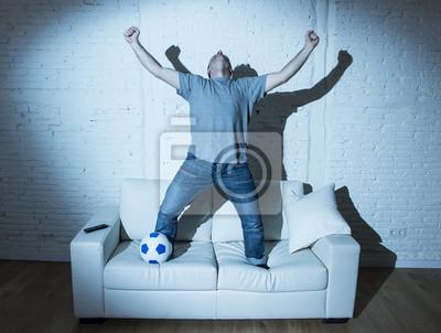 fanatykiem i szalony kibic oglądanie telewizji mecz piłki nożnej z piłką skoki na kanapie obchodzi cel