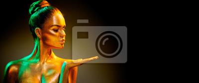 Fasonuje model dziewczyny w kolorowych jaskrawych złotych błyskotach pokazuje produkt na pustej ręce. Pusta przestrzeń kopii. Portret piękna dziewczyna z rozjarzonym makeup. Blask żywej neonowej skóry