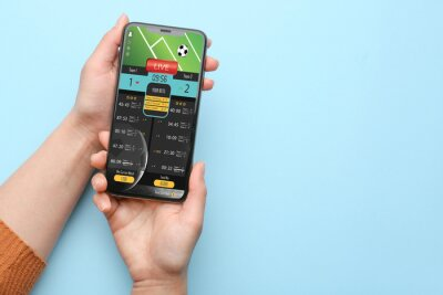 Naklejka Female hands with open page of online betting site on screen of mobile phone against color background