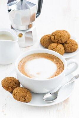 Naklejka filiżanka cappuccino i makarony na białym drewnianym stole