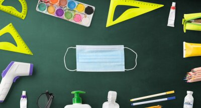 Flat lay top view of face mask and school supplies, back to school and coronavirus concept.