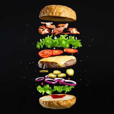 Naklejka Floating burger isolated on black wooden background. Ingredients of a delicious burger with ground beef patty, lettuce, bacon, onions, tomatoes and cucumbers