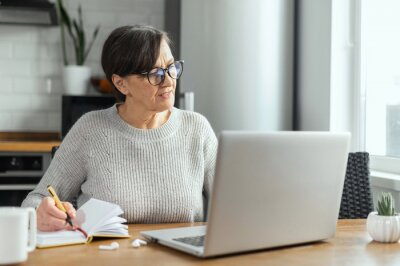Naklejka Focused retired woman is learning online, using a laptop for watching online classes, webinar, senior female takes a notes sitting in the kitchen at home