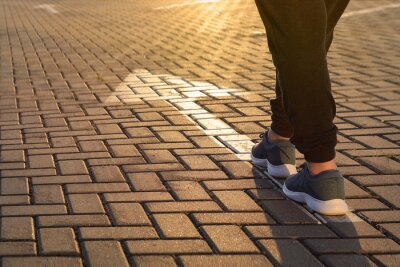 Naklejka Forward moving. Feet on road arrow in the rays of setting sun