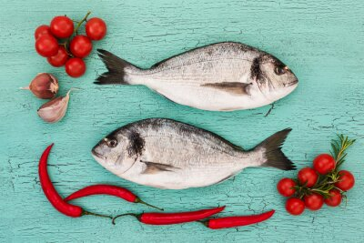 Naklejka Fresh dorado ryba z warzywami na niebieskim stole. Kopia przestrzeń, widok z góry