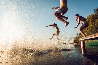 Naklejka Friends having fun enjoying a summer day swimming and jumping at the lake.